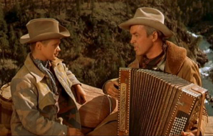 """Kid looking at Jimmy Stewart playin' accordion, both in dusty """"cowboy"""" outfits."""
