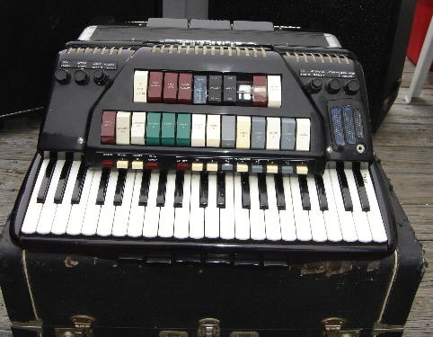 The front grill of a chordovox-style accordion, with many electric-organ switches.