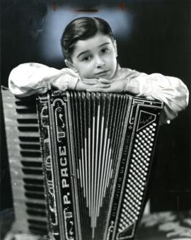 Studio portrait of cute kid with accordion.