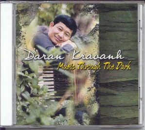 Daran Kravanh sitting in a forest with his beat-up accordion
