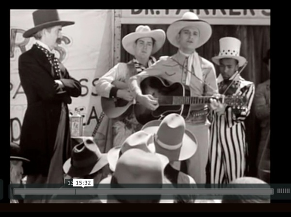 """Outdoor stage with performers in """"western"""" gear, and an African American fiddler in an Uncle-Sam costume."""