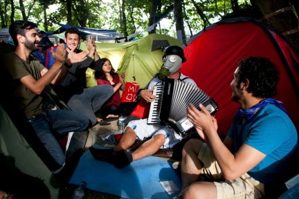 A demonstrator wearing a gas mask plays the accordeon as he sits with others near a tent at a makeshipt camp on Taksim square in Istanbul on June 7, 2013. (GURCAN OZTURK/AFP/Getty Images)