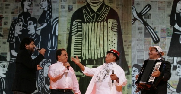 Dominguinhos and Luis Gonzaga on stage in front of a big accordion-player backdrop at a festival