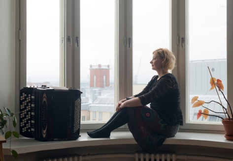 Maria Kalaniemi and her accordion in a window seat.