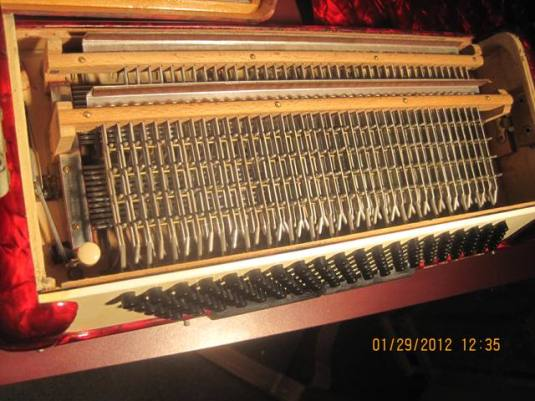 Internals of the bass side of an accordion with hundreds of buttons and metal rods.