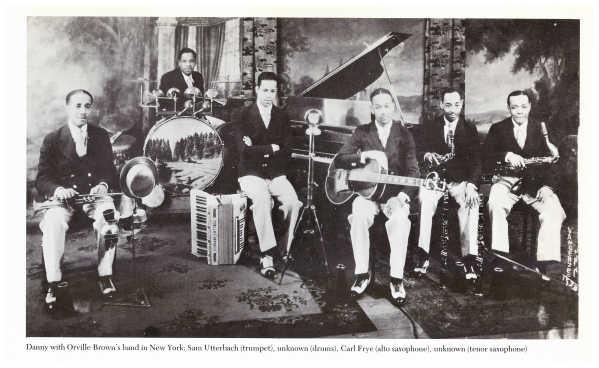 1930s jazz band. 6 black men with trumpet, drums, accordion/piano, guitar, 2 saxes