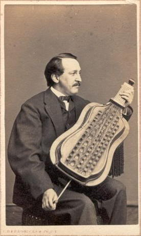 photo of man in 1860s suit, bowtie, mustache, holding a small cello-shaped melophone on his knees as if playing a guitar. With his left hand on the buttons on the neck, and his right hand pumping the bellows using a handle at the bottom of the instrument near his right knee.