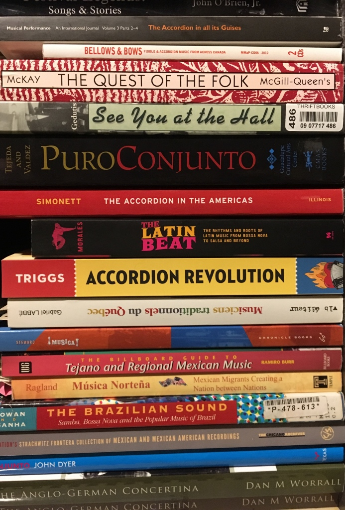A stack of books (photo of my bookshelf turned vertically) Includes Accordion Revolution, and a dozen other books referenced in my bibliography.  Including: See You At the Hall, Puro Conjunto, The Quest of the Folk, Musica Norteña, The Accordion in the Americas, Musicians Traditionnels du Québec