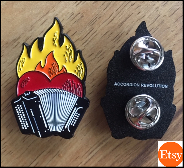 (Small orange 'Etsy' logo in bottom right.) Photo: Flaming Heart Accordion pin, front black and white 3row button accordion, red heart, with orange and yellow flames. Two pin holders on the back, with tiny 1pt all caps: 'ACCORDION REVOLUTION'