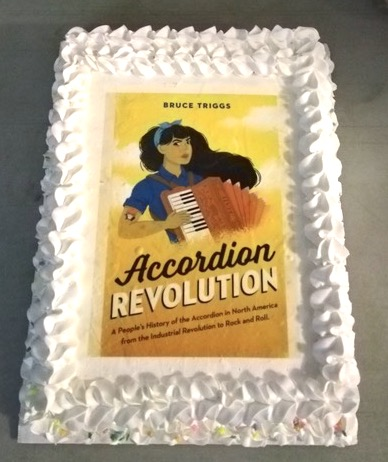 Photo of a fancy (ice-cream) cake from above. It is rectangular with fluffy white icing trim on the sides. Imprinted on the center is the cover image of the Accordion Revolution book.