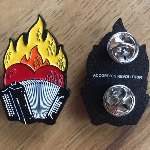 """Flaming Heart Accordion pin, front black and white 3row button accordion, red heart, with orange and yellow flames. Two pin holders on the back, with tiny 1pt all caps: """"ACCORDION REVOLUTION"""""""