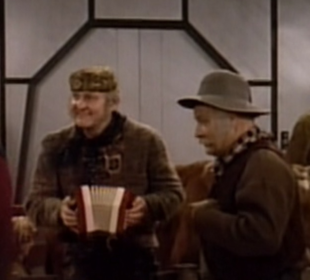 Screenshot from TV show: Cheap late 20th Century concertina, played by a cheerful white man with mutton-chop sideburns