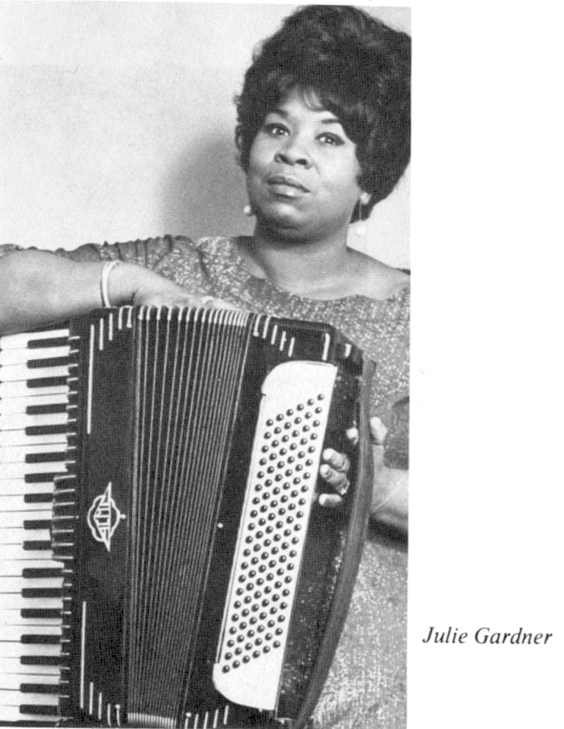 Black and White Photo of Julie Gardner. Black woman in a dress and jewelry half-smiling holding a 120 bass piano accordion.