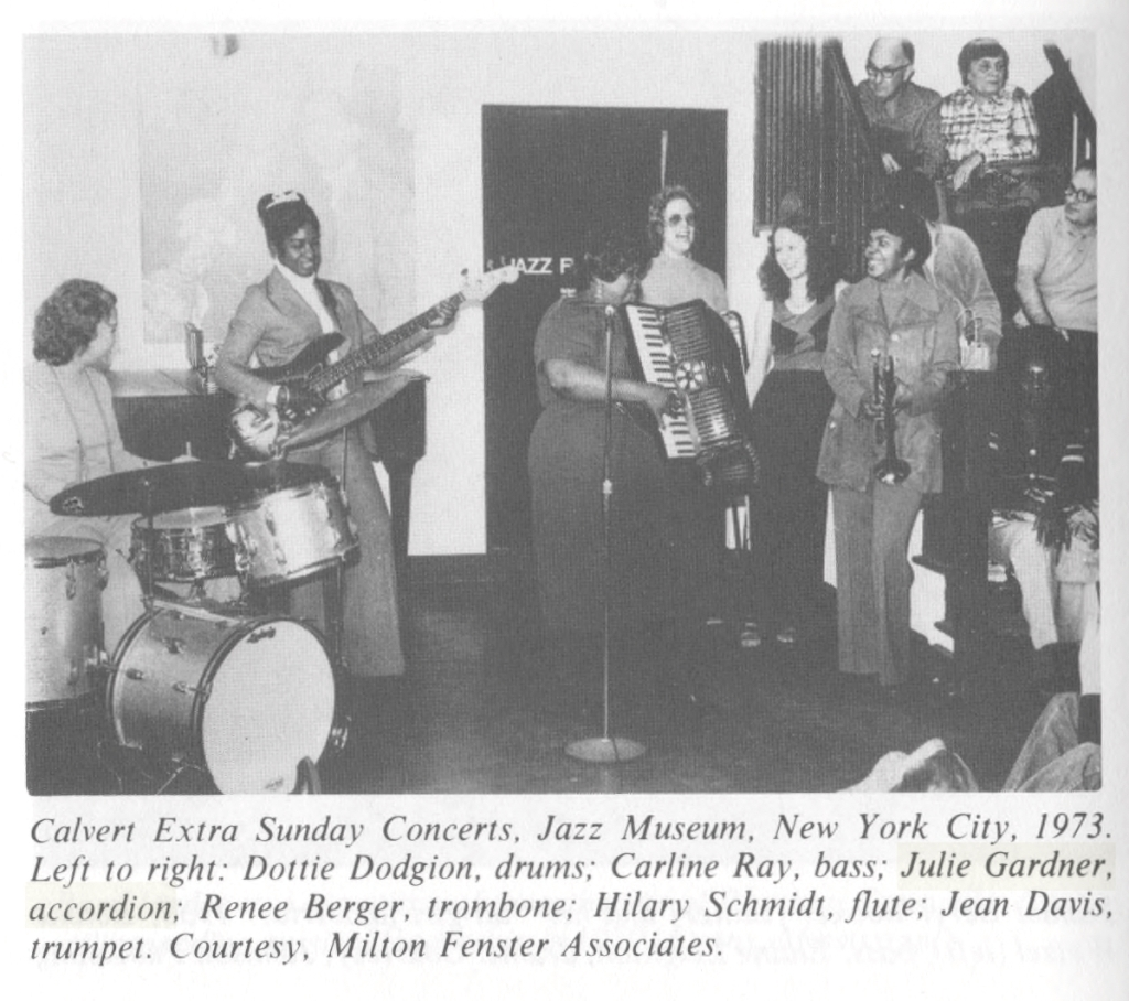 "Black and white photo of a band set up in an indoor space. Audience members can be seen standing behind them and sitting on a stairway to the right. Caption: ""Calvert Extra Sunday Concerts, Jazz Museum, New York City, 1973. Left to right: Dottie Dodgion, drums: Carline Ray, bass; Julie Gardner, accordion; Renee Berger, trombone; Hilary Schmidt, flute; Jean Davis, trumpet. Courtesy, Milton Fenster Associates."""