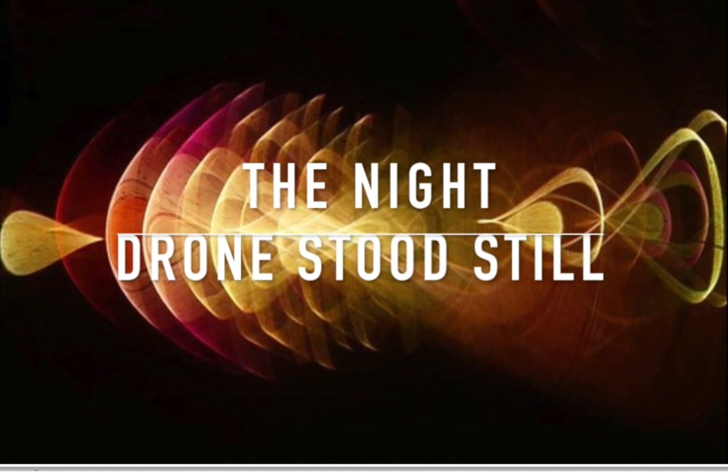 """The Night Drone Stood Still"" (missing a ""the""). Title screenshot from the promotional video for this episode. Background is an elaborate abstract image by Megan Carsience. It looks like interlacing golden-brown waves of light in front of a dark background."