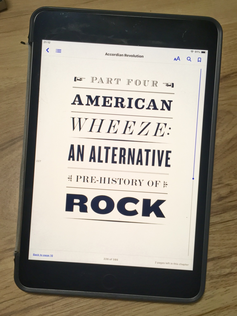 "Photo of an ebook reader showing a chapter-title page with lettering like and old poster. Text: ""Accordion Revolution, Part Four, American Wheeze: An alternative pre-history of rock."""