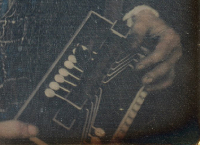 "Detail of the ""Women with Accordion"" photo. Shows the accordion in her hands, but not very clearly. The instrument has visible pallets but you can't see how the buttons are laid out."