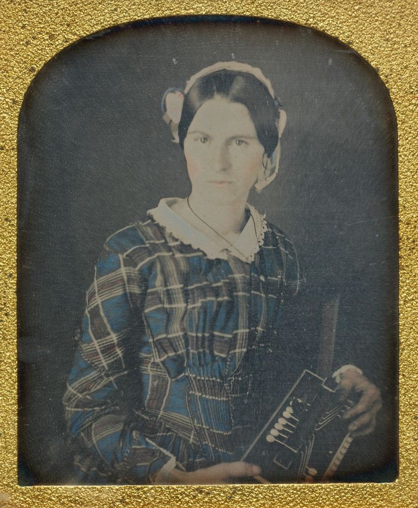 Black and white mage in a golden frame. Woman in colorized red and blue plaid dress. Straight dark hair pulled back behind a ribbon or hat on the back of her head. She is holding an odd accordion that is hard to see the details of.