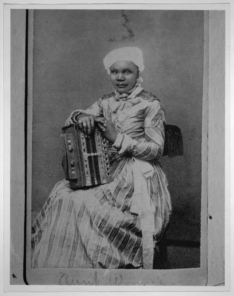 Antique black and white photo of a seated African American woman in a long formal-looking dress and hat. Holding a large diatonic button accordion on her lap. Instrument has two bass buttons, but the right hand buttons aren't visible. Seems like a fairly intricately designed model from the 1890s-1910s maybe?